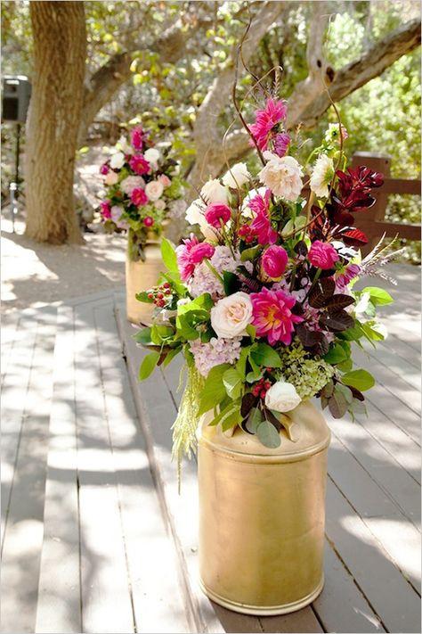 gold painted milk cans holding wedding floral arrangements