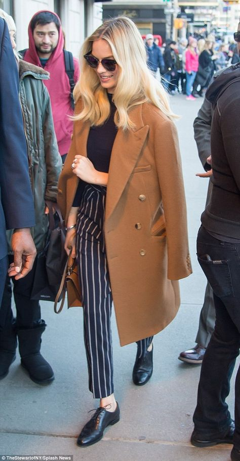 Casual chic: As she sashayed into the venue, the blonde beauty was toting a caramel leather satchel bag to match her coat, and shielded her eyes behind a pair of dark round sunglasses