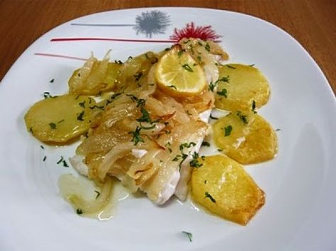 Merluza encebollada al horno / 1 cola de merluza. Aceite. 2 cebollas. 2 dientes de ajo. 2 patatas. Sal. Vino blanco. Limón.