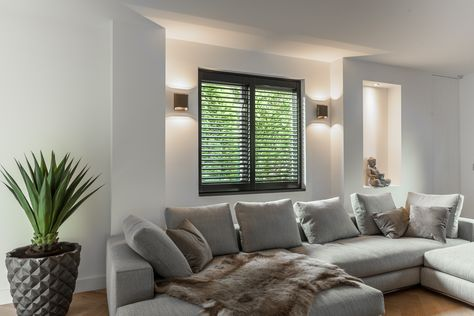 Zwarte shutters in moderne woonkamer. Wandverlichting naast raam ...