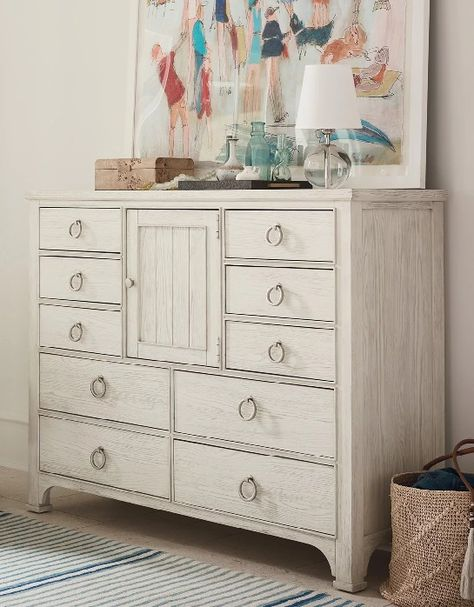 Add some unique coastal style to your bedroom with this Sandbar finished dressing chest. Bordering on both casual and contemporary stylings, this piece carves out its own place in a bedroom with the metallic ring pulls on all ten of the drawers. This chest's unique style and storage capacity is further illustrated by the center door that conveniently opens to reveal an adjustable shelf.