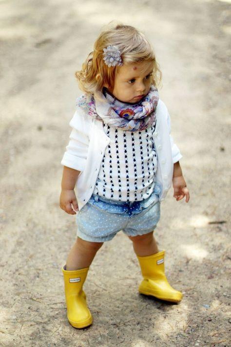 bébé fille avec short en jean à pois et bottes en caoutchouc jaune