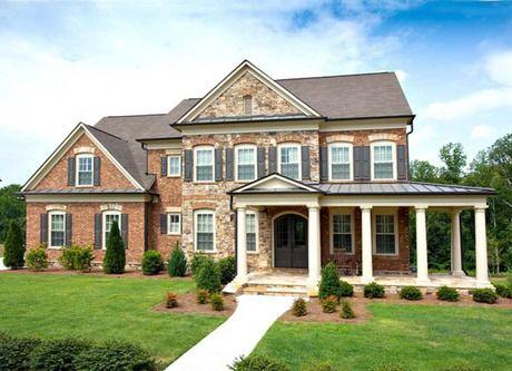 Six pillars define a wrap-around porch on this brick and stone home. The  Olmsted new home community by John Wieland Homes in Huntersville, NC.