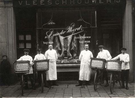 Het personeel van slagerij A. van der Weerd aan de Huidenstraat in Amsterdam poseert voor de etalage van de winkel in witte jassen met transportfietsen. In de etalage een aantal opgehangen karkassen. Nederland, 1917.