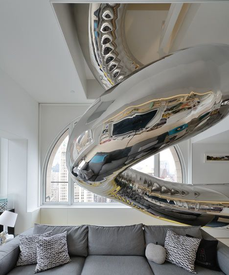 A tubular steel slide plummets through four storeys inside this penthouse apartment in New York