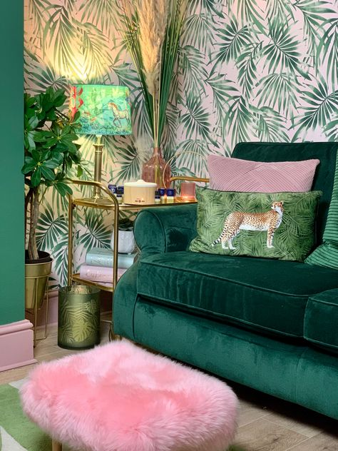 The green velvet sofa is complimented by the palm leaf wallpaper with a blush background. Using the retro drinks trolley as a side table adds a vintage vibe, along with the pink coloured glass vase and tealight holder.