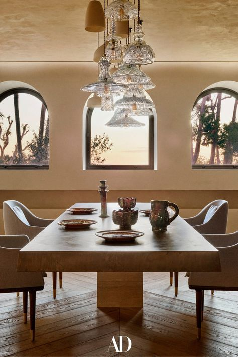 When they were ready to downsize from their nearby villa, a couple turned to their architect son to combine three stellar apartments into their dream home. In the dining room, the large ceiling suspension is a unique piece by Les Penates. The ceramic plates are by Nicola Fasano of Fasano Ceramiche while the vintage ceramic jugs and candlestick are from Morocco. #diningrooms #diningroomideas #design #diningtables #diningchairs #windows #minimalist #villas #plates #vintage #ceramic #candles