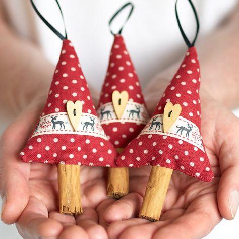 Apportez quelques décoration de Noël naturelle dans votre maison avec notre charmantes ornements de Noël fait à la main. Fait en forme d'arbres rustiques avec des troncs d'arbres de bâton de cannelle véritable pour à la fois le style et le parfum d'un Noël traditionnel. Ces arbres sont faits de tissu en lin rouge à pois, agrémenté de ruban de renne et coeur en bois en forme de boutons. Chaque arbre a été bourré de fibres de polyester et a une boucle de ruban noir sur le dessus pour…