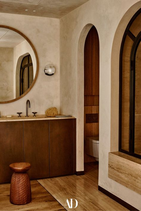 In the guest bathroom, sconces by Kelly Wearstler were included. Both the basin in travertine stone with oak bronze effect cupboards and the bath were made to measure. The faucet is from the Watermark Collection. #bathrooms #guestbathrooms #bathroominspo #design #architecture #minimalist #wood #arches #mirror #stools #bronze #cupboards #bath #baths #bathrub #faucet #sink