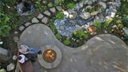 Pool converted into a rain-storing, water-wise tropical garden. Fire pit gives it some life.
