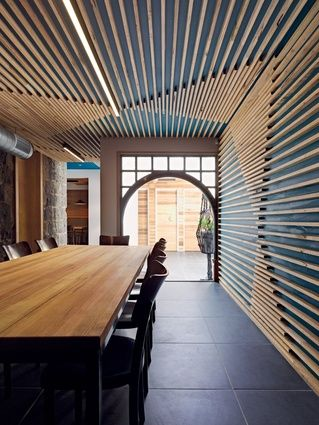 Timber battens line the walls of the private dining room, The Press. By SMLWRLD architects
