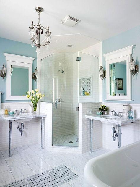 Une salle de bains turquoise avec douche en angle.