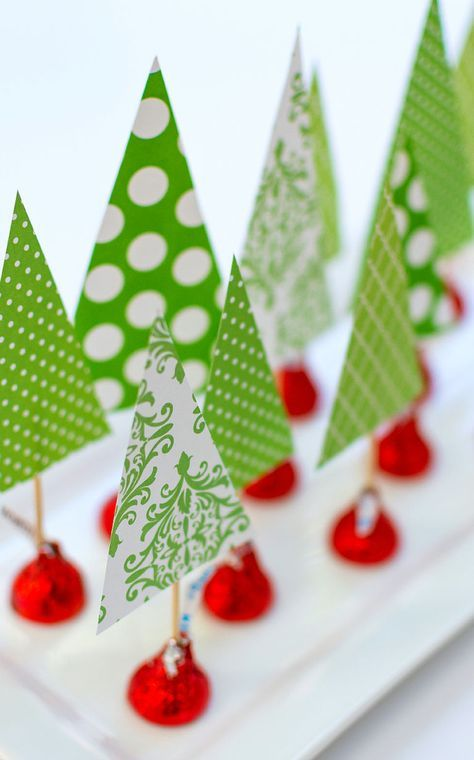 Bring the fun for the kids with this super simple and festive way to create a Christmas table centerpiece. All you'll need is scrapbook paper, toothpicks, tape, and red foil-wrapped Hershey's Kisses. See more at It All Started With Paint.