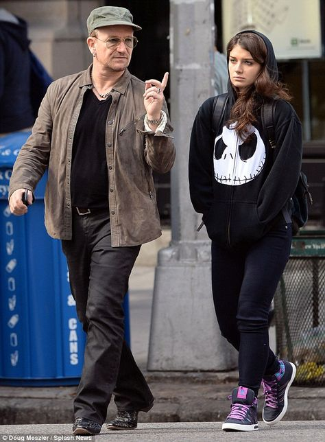 Bono gestures as he walks in New York with daughter Eve. She looks so bored with Dad.