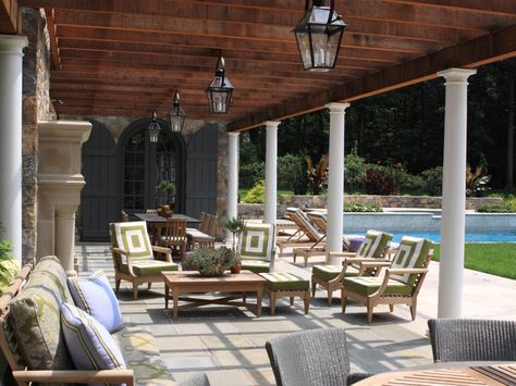 A stunning patio beneath a gorgeous wooden pergola gives this backyard luxurious appeal. Several seating zones offer areas for eating, sitting with friends and family, or just enjoying the view. Perfectly spaced lanterns assure the fun can continue into the night.