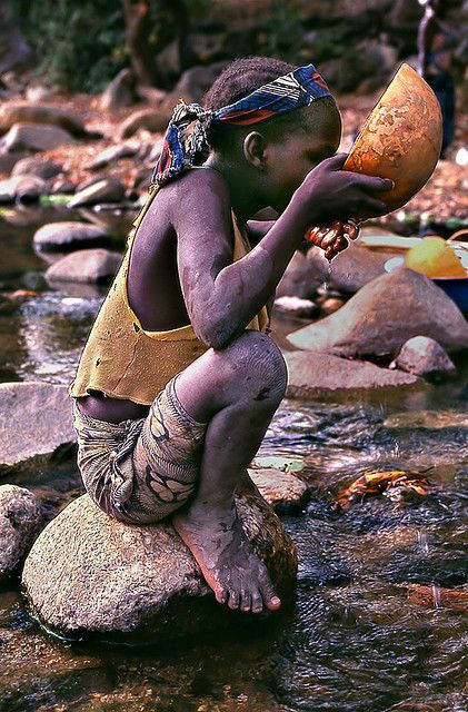A girl stops for a drink in a river in Cameroon, Africa. A member of Gondwana DMCs - your network of boutique Destination Management Companies across the globe - www.gondwana-dmcs.net
