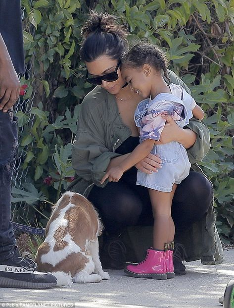 On Sunday little North West looked absolutely besotted with an adorable pooch at the Brentwood farmers market in Los Angeles as her parents Kim Kardashian and Kanye West looked on with pride