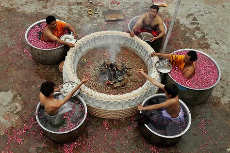 Hindu priests perform rituals as they pray for monsoon rains at a temple