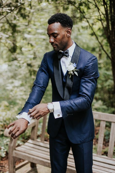 Navy Blue Tux accented with a white and blue boutonniere, a silver watch, cufflinks, and a bowtie. Photography: Van Elk & Co. Planner: Boldly Chic Events #summerwedding #outdoorceremony #weddingday #groom #boutonniere #groomboutonniere #wedding #indianapolisweddingplanner #nycweddingplanner #boldlychicevents