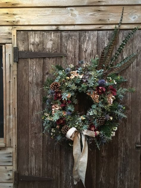 Christmas wreath with eucalyptus, orchid flowers, fir branches, sea holly, roses, pine cones and pheasant feathers