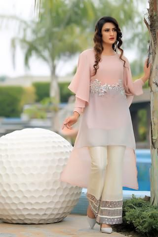 Tea pink and grey georgette chiffon high low top with pearl embroidery on waist line Included is a tea pink slip Ivory raw silk trousers with ombre flare with sequined embroidery Available to order as boot cut, straight trousers or cigarette tr