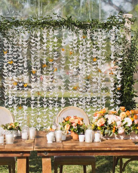 13 Wedding Details With International Flair | When décor combines with tradition, it adds so much more unique meaning and sentiment to a wedding. Inspired by an ancient Japanese legend, this wedding backdrop features one thousand origami cranes for good luck.