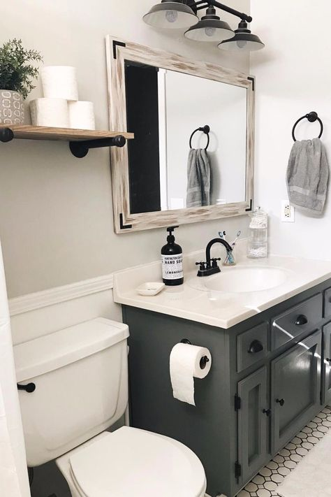 This guest bathroom uses a stunning charcoal color for its vanity. The color is trendy, modern and it's now. The floating shelf with the rustic mirror throw in some farmhouse flare. White hexagons on the floor add some depth and texture to the space. Guest Bathrooms, Upstairs Bathrooms, Downstairs Bathroom, Bathroom Renos, Bathroom Renovations, Home Remodeling, Remodel Bathroom, Boho Bathroom, Small Bathroom Ideas