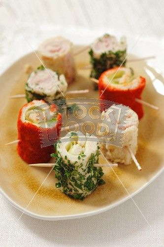 Toast rolls filled with ham and cheese, covered with pepper, parsley and almonds
