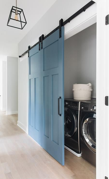 White Hallway With Blue Barn Doors On Rails Opening Into A Laundry Closet Featuring A Silver Front Lo Laundry Room Doors Laundry Room Closet Tiny Laundry Rooms