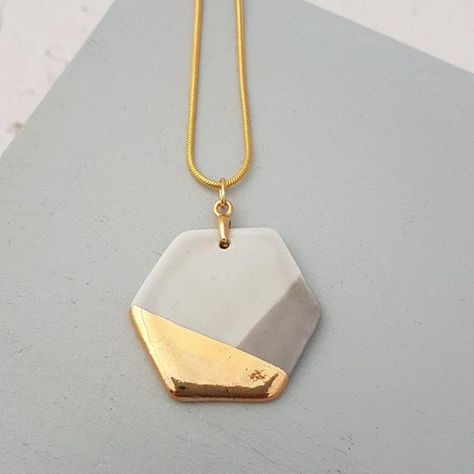 A two tone grey glazed porcelain pendant with 22k gold lustre detail. The porcelain pendant is attached to an 18 inch gold plated snake chain with extender.  The pendant is fired 3 times to achieve this finish. The lightweight nature of this clay makes the necklace very easy and durable