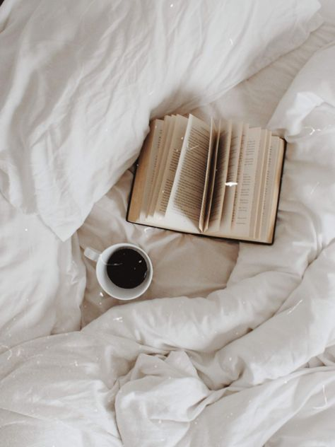 Flat lay: book, bed, black coffee, white bedding