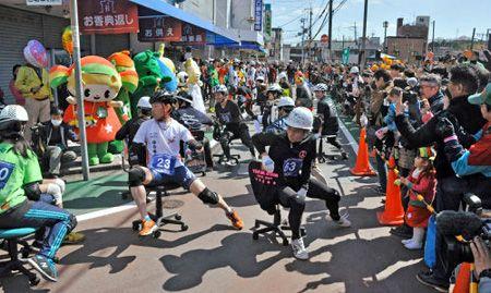 いす-1GP(グランプリ) 沿道の声援を受け、事務いすで疾走する参加者たち(京田辺市河原・キララ商店街)
