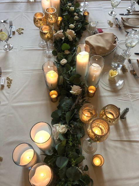 Greenery garland with gold glitter pedestal votives, gold votives, pillar candles and blooms tucked in.   #weddingflorist #milwaukeeweddingflorist #wisconsinwedding #weddingphotography #mkewedding #mkebride #marriedinmke #mkeflorist #wisconsinflorist #wisconsinbride #premierbride #stylemepretty #milwaukeewedding #elegantwedding #milwaukeebride #feistyflowers #weddingtabledecor #weddingreception #floralarrangement #garland #greenerygarland #headtable #tablescape #eucalyptusgarland