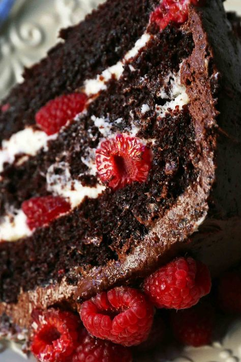 Rich chocolate cake layered with whipped cream cheese raspberry filling, topped with creamy chocolate frosting and fresh raspberries.