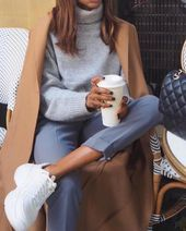 Classic camel coat over casual gray knit sweater and blue pants with comfy sneak...