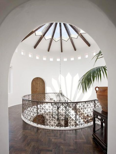 The second floor landing of a Mediterranean estate in Santa Barbara.  Stunning skylight with cathedral ceiling cupola and Moroccan style iron railing along with herringbone hardwood wood floors. Love! Go to blog to see rest of house! http://cococozy.com