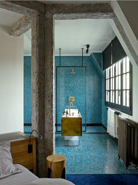 Au cœur de Paris, ce duplex haut perché a été réhabilité par Studio Ko sous le signe du contraste. Conçue comme une salle d'eau orientale, cette salle de bains est tapissée de carreaux de mosaïque bleus et dorés (Bisazza) © Philippe Garcia
