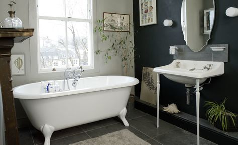 A crisp white clawfoot bathtub and console sink brighten up this vintage-inspired space. A black accent wall and gray slate floors bring just the right amount of drama. Shop the look at our Wayfair Boutique.