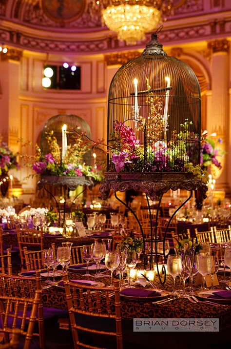 Fabulous birdcage wedding centerpieces are filled with candles and pink