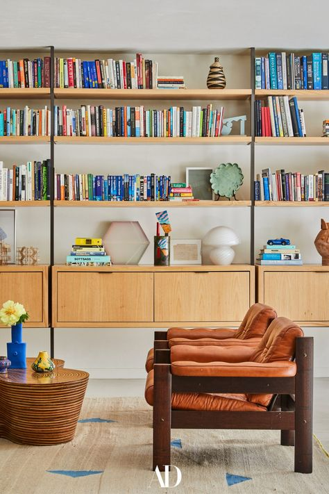 While most of the decor in this Coral Gables home is new, a set of vintage leather accent chairs is one notable exception. The family brought them with them to Connecticut and back to Florida again to be part of Bunsa's final composition. #livingrooms #livingroominspo #livingroomideas #design #books #library #shelving #vintage #leather #rugs #chairs #armchairs #wood #color #florida