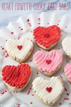 Heart Funfetti Cookie Cake Bars - delightfully chewy sprinkle-filled sugar cookie cake bars topped with fluffy buttercream show your love for your friends and family with these easy customizable delish heart treats. #valentinesday #hearts #funfetti #confetti #sprinkles #cookiecakebars #cookiebars #heartfunfetticookiebars #heartfunfetticookiecakebars #valentinesdaydesserts #buttercream  Heart Funfetti Cookie Cake Bars - delightfully chewy sprinkle-filled sugar cookie cake bars topped with fluffy