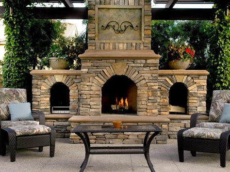 This stunning patio fireplace is nestled under a pergola and surrounded by lots of greenery.