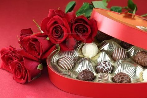 Heart shaped box filled with a variety of candies and long stem roses against a red background. Selective focus on candy.