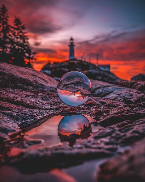 A lighthouse beautifully reflected in a puddle of water on the coast of Vancouver, Canada. Through the Lensball.