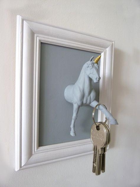 Accroche-clés : licorne gris clair sur fond gris foncé et cadre blanc