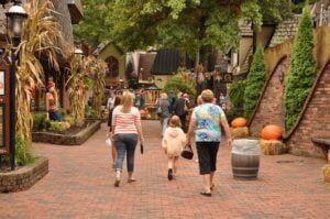 A Family Walking Through The Village In Downtown Gatlinburg In 2020 Smoky Mountains Attractions Gatlinburg Trails Gatlinburg