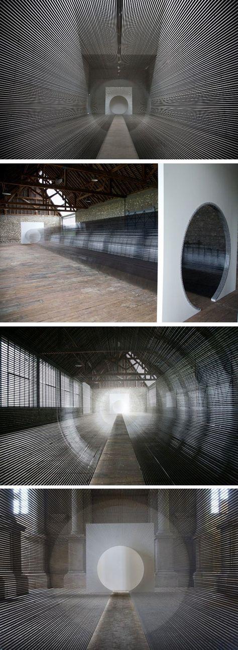 Un tunnel de bobines de cassettes VHS  Zilvinas Kempinas est un artiste lithuanien qui vit et travaille à New York et qui s'intéresse à l'art cinétique, expérimentant les possibilités de mouvements dans l'oeuvre d'art. Dans son installation Tube, il utilise des bandes magnétiques qu'il tend à chaque extrémité des deux murs qui ont été préalablement percés de manière circulaire.