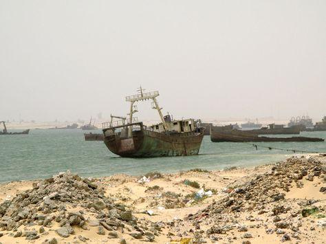 - Dans la rade de Nouadhibou, un gigantesque cimetière marin nargue et gêne les pêcheurs. Au début des années 1980, lors de la nationalisation du secteur de la pêche, des armateurs étrangers y ont abandonné près de 200 bateaux vétustes.