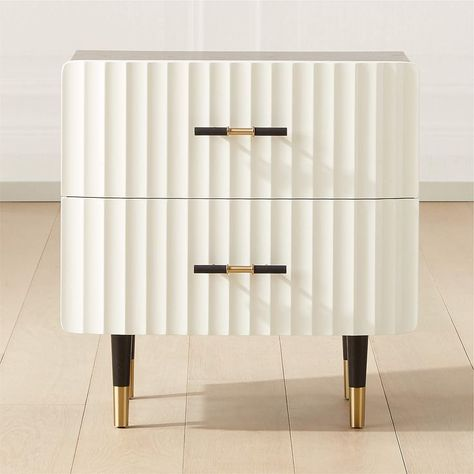Ebonized oak frames this black and white Caleb Zipperer-designed nightstand in stark contrast. Two wavy hi-gloss white drawers tuck away necessities. Brass handles with black faux leather detail complete the elevated look. Learn more about Caleb Zipperer on our blog. CB2 exclusive.