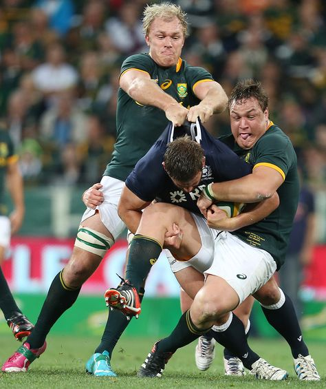 Schalk Burger and Coenie Oosthuizen of South Africa drag down Scotland's Chris Fusaro
